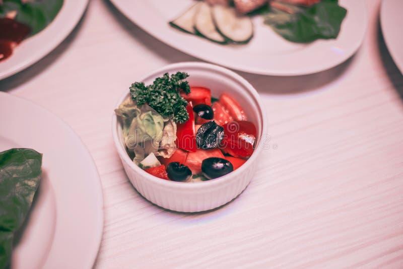 Ensalada de las verduras frescas en un cuenco blanco en la mesa de comedor imagen de archivo libre de regalías
