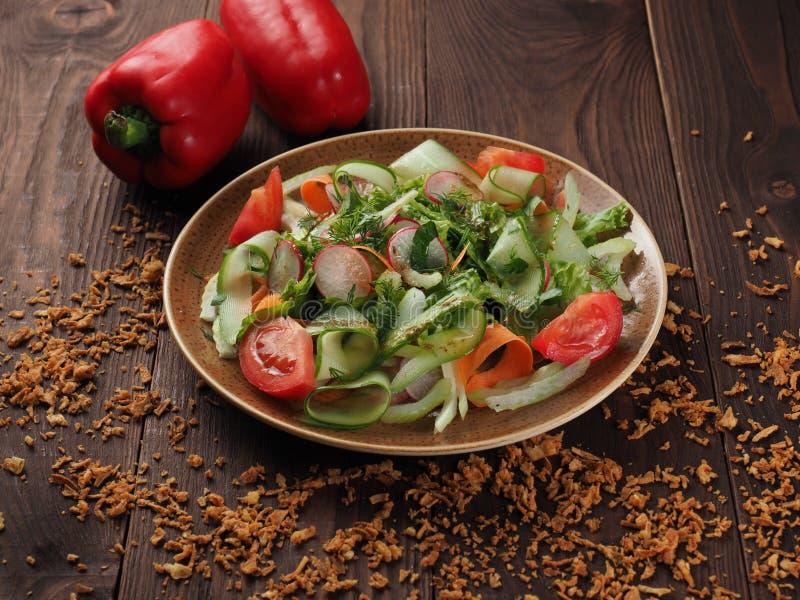Ensalada de las verduras frescas en una placa en la tabla imagen de archivo