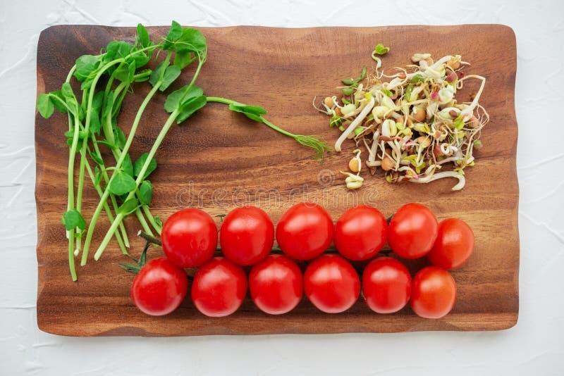 Ensalada de los brotes de la semilla de diversas plantas con los brotes de haba y los tomates de cereza en un tablero de madera L fotos de archivo libres de regalías
