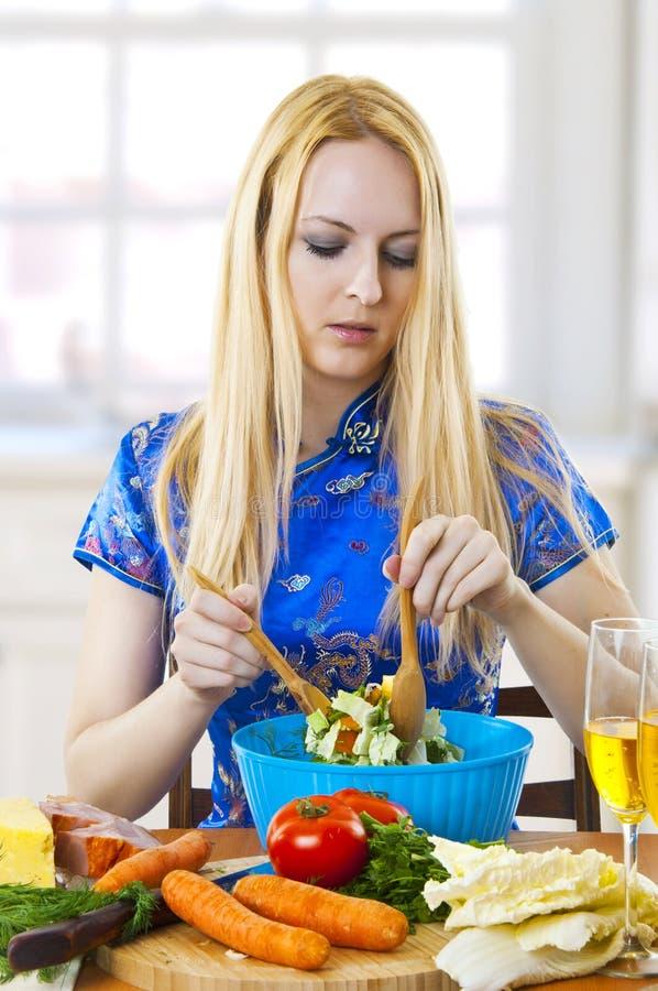 ensalada de mezcla de la mujer joven en cocina fotografía de archivo libre de regalías
