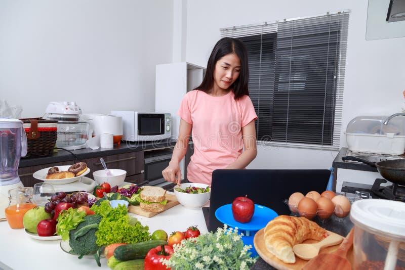 Ensalada de mezcla de la mujer mientras que cocina con el ordenador portátil en cocina foto de archivo libre de regalías
