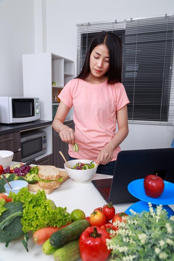 Ensalada de mezcla de la mujer mientras que cocina con el ordenador portátil en cocina fotos de archivo