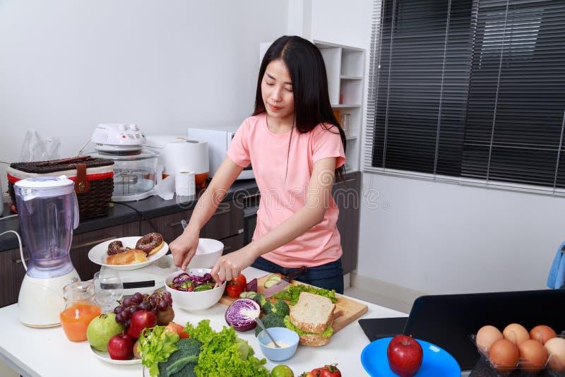 Ensalada de mezcla de la mujer mientras que cocina en cocina imagen de archivo libre de regalías