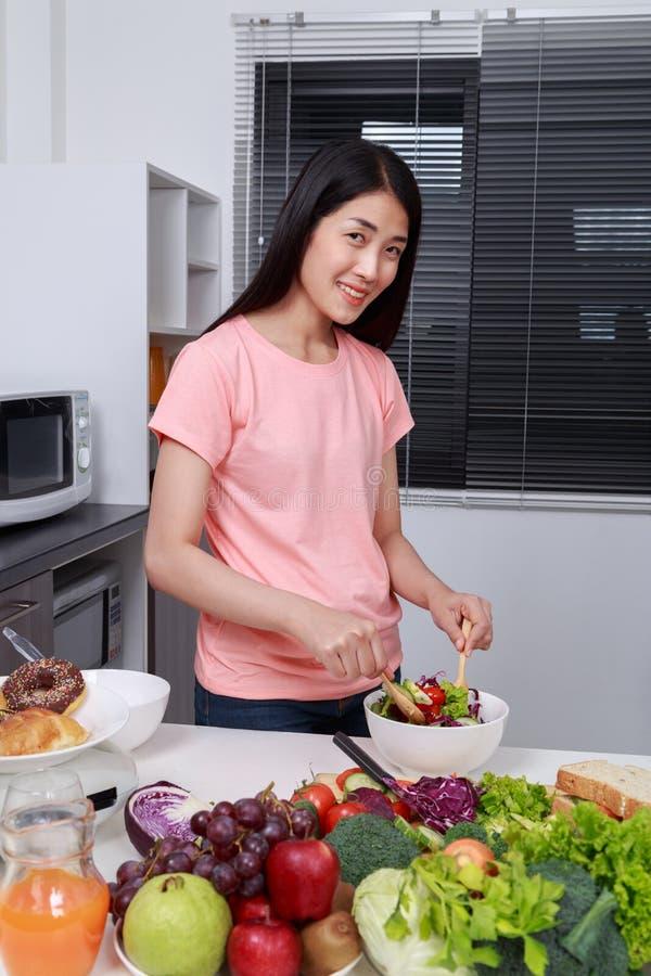 Ensalada de mezcla de la mujer mientras que cocina en cocina foto de archivo