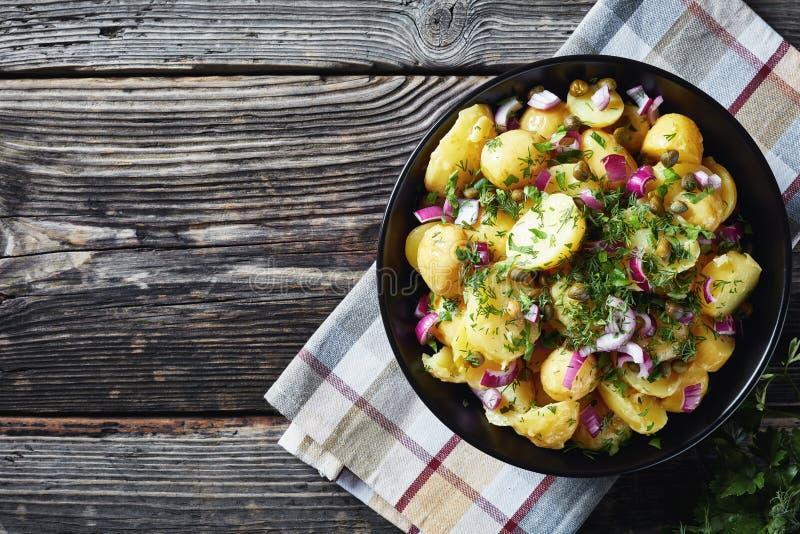 Ensalada de nueva patata con la cebolla roja, alcaparras, verdes imagenes de archivo