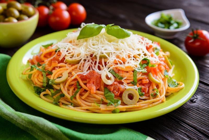 Ensalada de pasta de los espaguetis con la salsa de tomate, las aceitunas, el queso de Gouda y la albahaca imagen de archivo