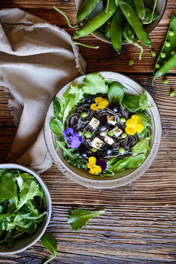 Ensalada de pasta de la alubia negra con verdes frondosos, aceitunas, los guisantes verdes, el queso de las ovejas y las flores c fotografía de archivo libre de regalías