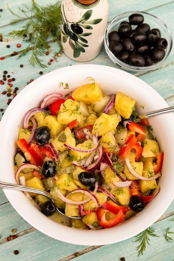 Ensalada de patata con la cebolla, las aceitunas, la pimienta, el pepino conservado en vinagre y el eneldo fotografía de archivo
