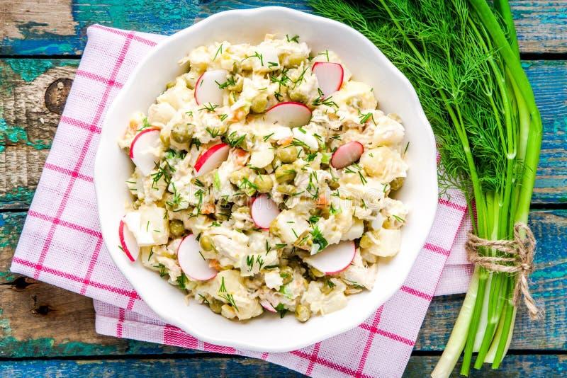 Ensalada de patata con los rábanos frescos en un cuenco blanco con eneldo y la cebolla verde imagen de archivo