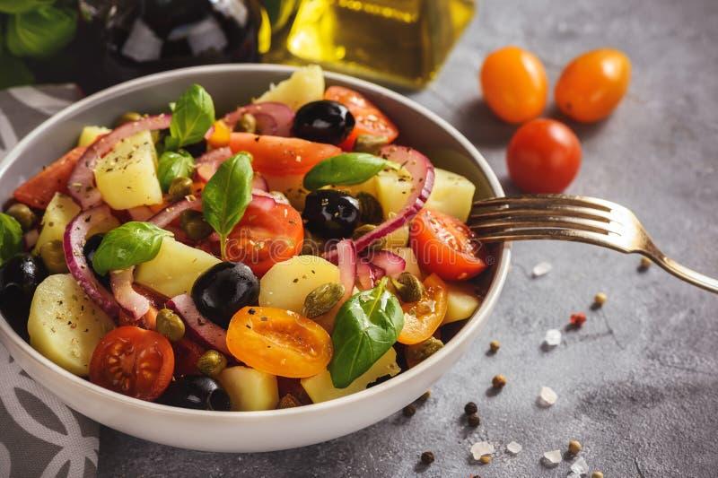 Ensalada de patata con los tomates, aceitunas, alcaparras, cebolla roja, cocina italiana del estilo Insalata Pantesca fotografía de archivo