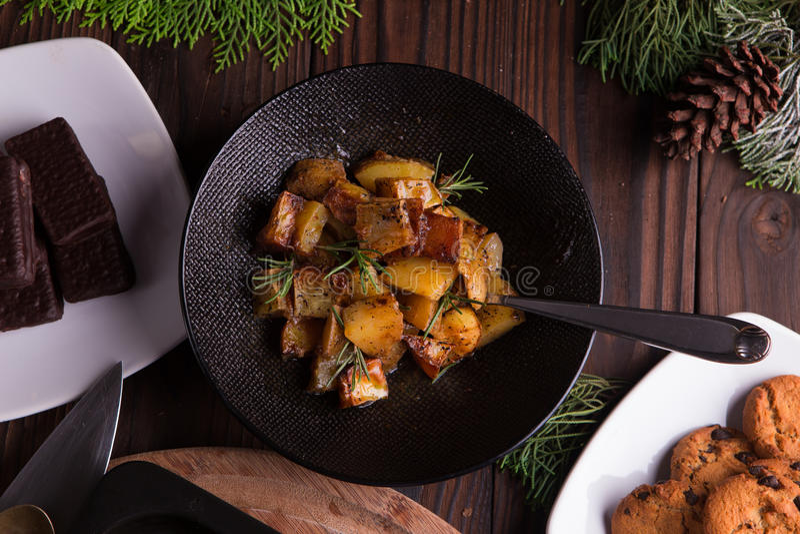 Ensalada de patata dulce salteada en el cuenco negro en fondo de madera marrón Acompañamiento para la Navidad, la acción de graci fotografía de archivo