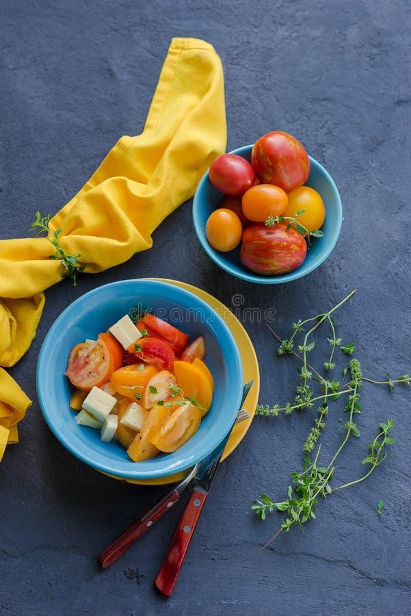Ensalada de tomates rojos y amarillos en un cuenco fotografía de archivo