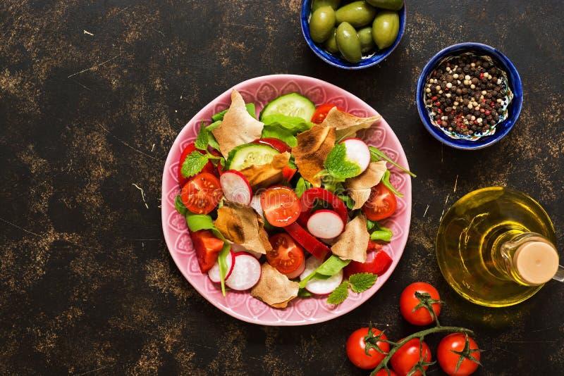 Ensalada de verduras frescas con el primer del fattoush del pan Fattoush árabe en un fondo oscuro, visión superior del plato foto de archivo libre de regalías