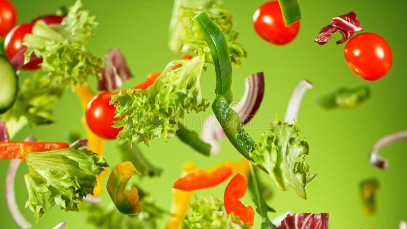 Ensalada de verduras voladoras aislada sobre fondo verde imágenes de archivo libres de regalías