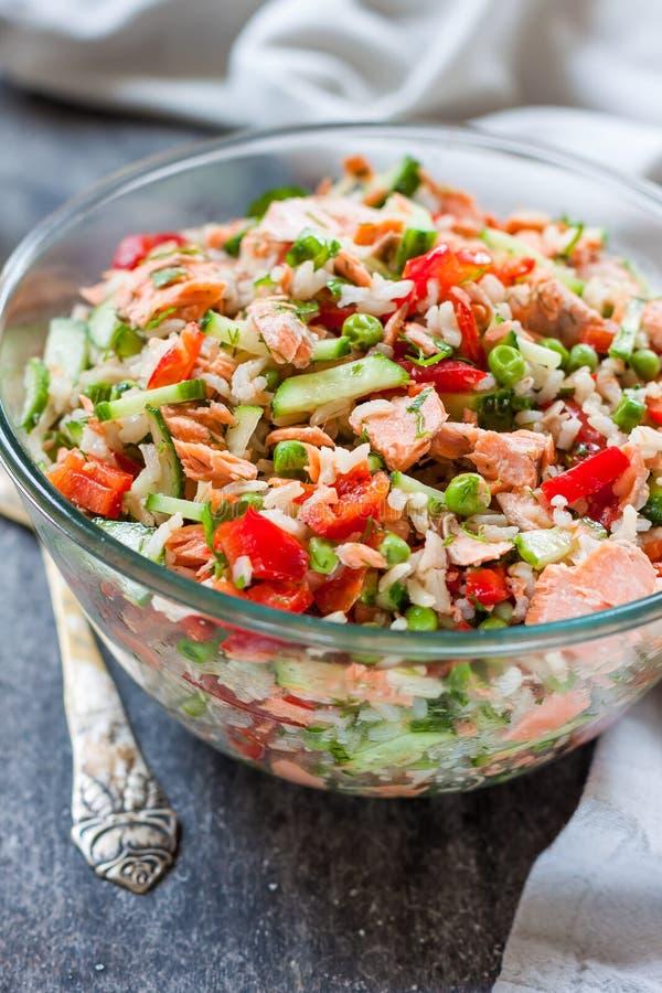 Ensalada del arroz con los salmones, los pepinos, los guisantes y el paprika, imagenes de archivo