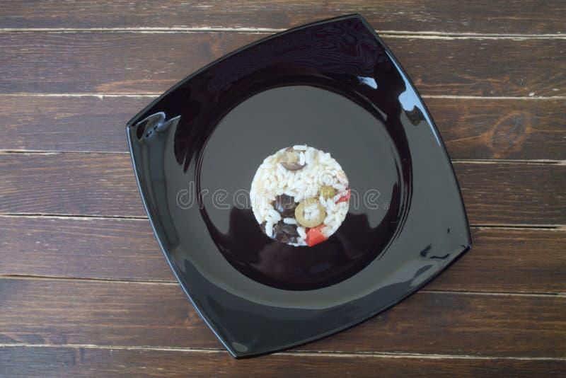 Ensalada del arroz en un plato negro en la madera desde arriba fotografía de archivo libre de regalías