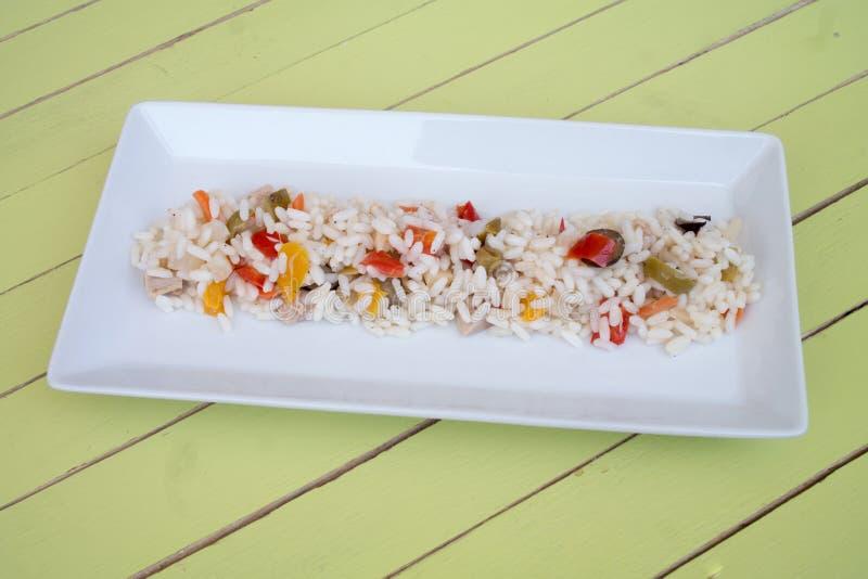 Ensalada del arroz en una bandeja blanca en la madera verde imagen de archivo libre de regalías