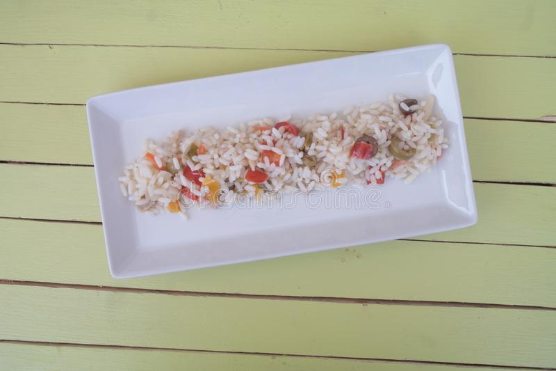 Ensalada del arroz en una bandeja blanca en la madera verde desde arriba imagen de archivo