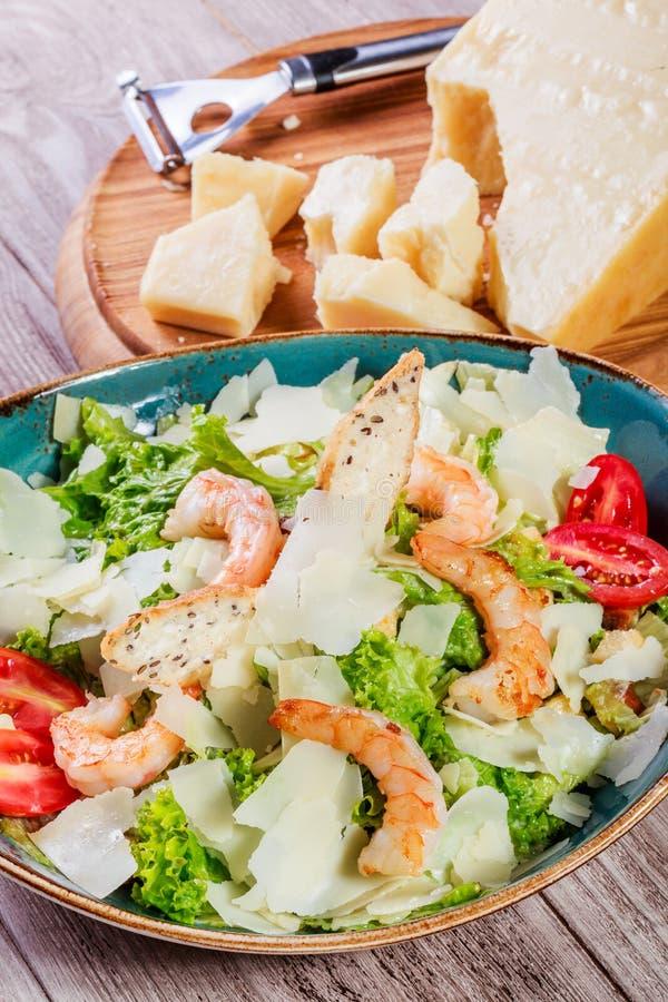Ensalada del camarón con el queso parmesano, los cuscurrones, los tomates, los verdes mezclados, lechuga y el vidrio de vino en f fotos de archivo