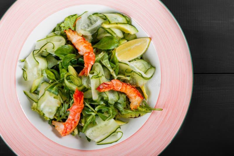 Ensalada del camarón con espinaca, los pepinos, el aguacate, el limón, el arugula, la lechuga y la salsa en placa en fondo de mad fotos de archivo