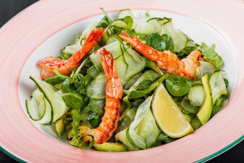 Ensalada del camarón con espinaca, los pepinos, el aguacate, el limón, el arugula, la lechuga y la salsa en placa en fondo de mad imagenes de archivo