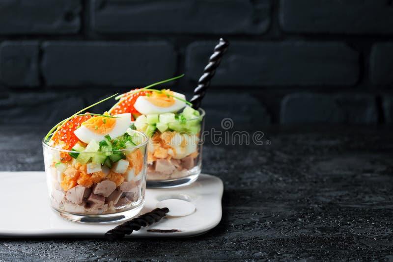 Ensalada del hígado de bacalao con los huevos, los pepinos y el caviar rojo en un vidrio fotos de archivo