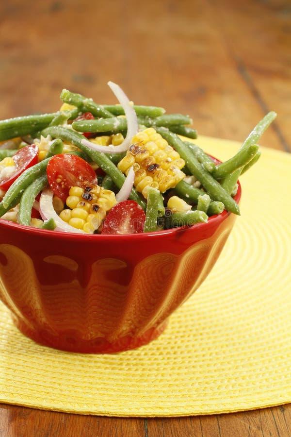 Ensalada del maíz asado a la parrilla y de la haba verde en el cuenco rojo en restaurante fotografía de archivo