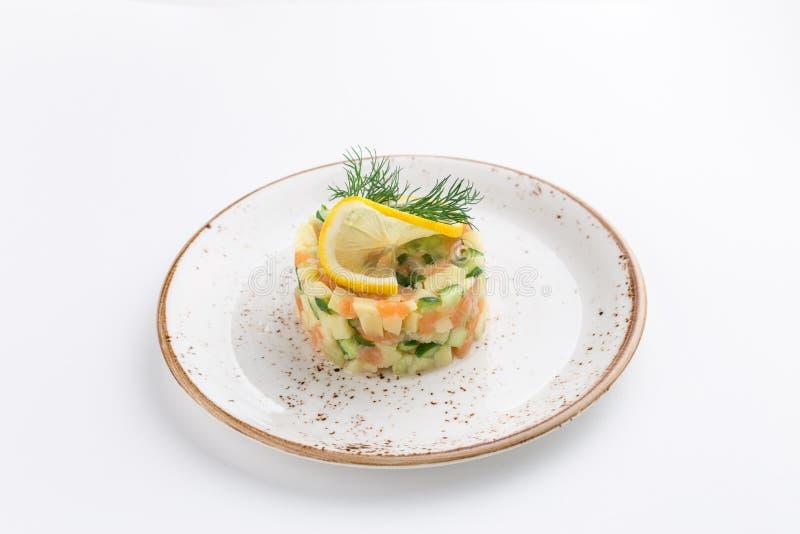 Ensalada del salmón ahumado con el pepino, los huevos y la rebanada de limón en el top aislado en el fondo blanco fotos de archivo