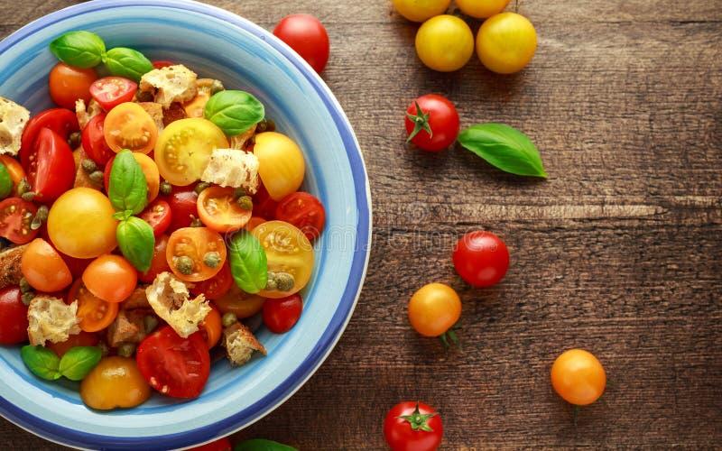 Ensalada del tomate de Panzanella con los tomates de cereza, las alcaparras, la albahaca y los cuscurrones rojos, amarillos, anar imagen de archivo libre de regalías
