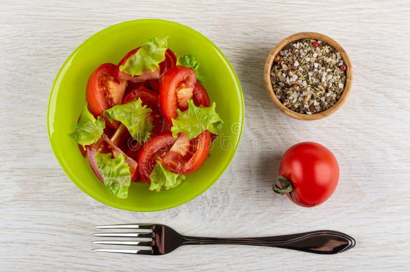 Ensalada del tomate, lechuga en el cuenco, cuenco con el condimento, tomate, bifurcaci?n en la tabla Visi?n superior fotografía de archivo libre de regalías