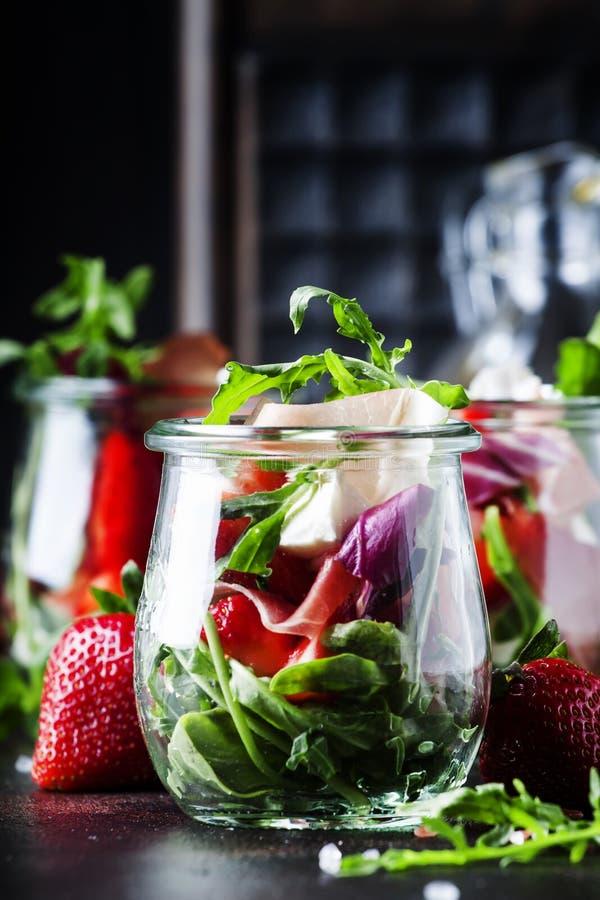 Ensalada del verano con arugula, queso suave, la fresa roja y el prosc imagen de archivo