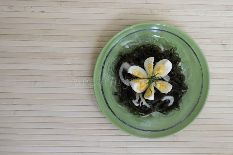 Ensalada delicioso sabrosa de la col del mar con un huevo hervido y las cebollas fotografía de archivo
