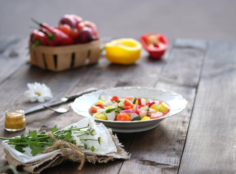 Ensalada en la placa y las verduras frescas en cesta foto de archivo libre de regalías