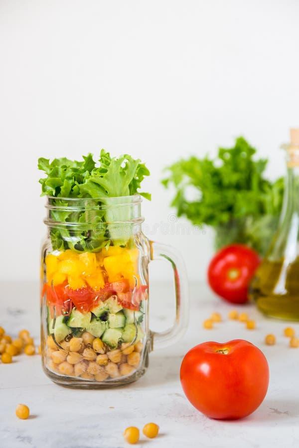 Ensalada en un tarro Ensalada sana hecha en casa del garbanzo, tomate, YE imagen de archivo libre de regalías