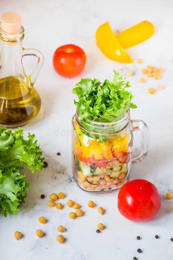 Ensalada en un tarro Ensalada sana hecha en casa del garbanzo, tomate, YE imagenes de archivo