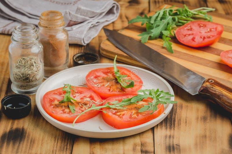 Ensalada Está fresco los tomates cortados con arugula y los condimentos en un cuenco blanco En un fondo de madera Foco selectivo fotos de archivo libres de regalías
