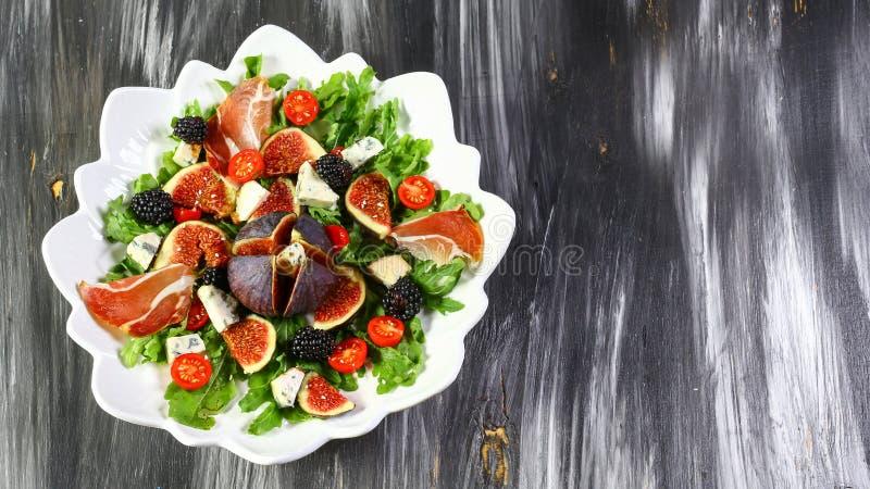 Ensalada fácil de la dieta con los tomates de los higos, de la hoja del arugula, del queso verde Dorblu, del prosciutto y de cere fotografía de archivo
