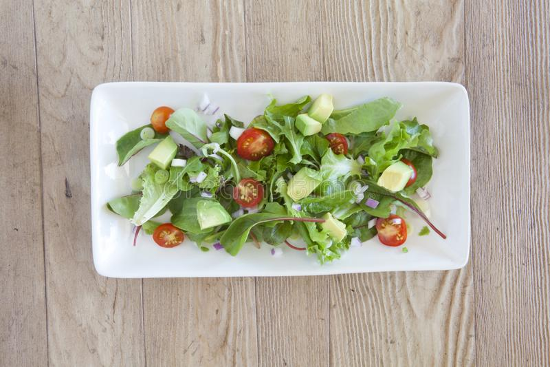 Ensalada fresca con el aguacate y los tomates imagen de archivo