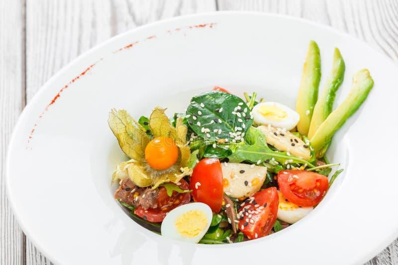 Ensalada fresca con el atún, espinaca, arugula, bacalao, alcachofas, huevos de codornices, aguacate, tomates de cereza, physalis  foto de archivo