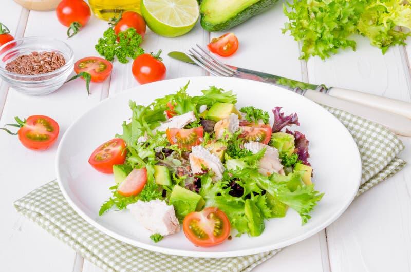 Ensalada fresca con el pollo, el aguacate, los tomates y las semillas de lino en una placa en el fondo de madera blanco fotos de archivo libres de regalías