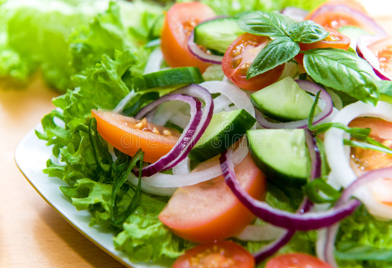 Ensalada fresca con la cebolla, el tomate y la albahaca imagenes de archivo