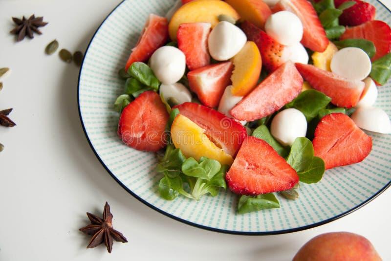 Ensalada fresca con la fresa, el melocotón y la mozzarella fotografía de archivo