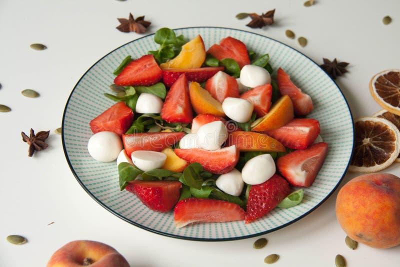 Ensalada fresca con la fresa, el melocotón y la mozzarella imagen de archivo