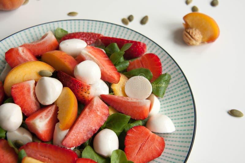 Ensalada fresca con la fresa, el melocotón y la mozzarella fotos de archivo