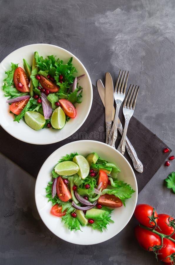 Ensalada fresca con los tomates, el aguacate y la granada fotografía de archivo libre de regalías