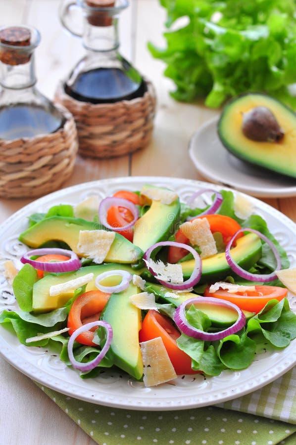 Ensalada fresca con los tomates, la lechuga, las cebollas, el aguacate y el queso parmesano foto de archivo