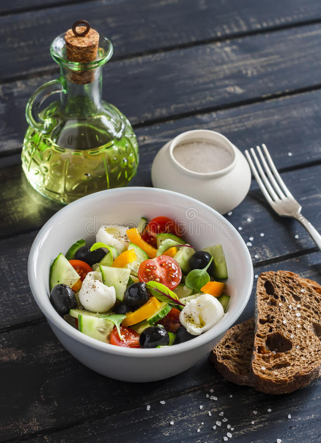 Ensalada fresca con los tomates, los pepinos, las pimientas, las aceitunas y el queso en un cuenco de cerámica imagen de archivo