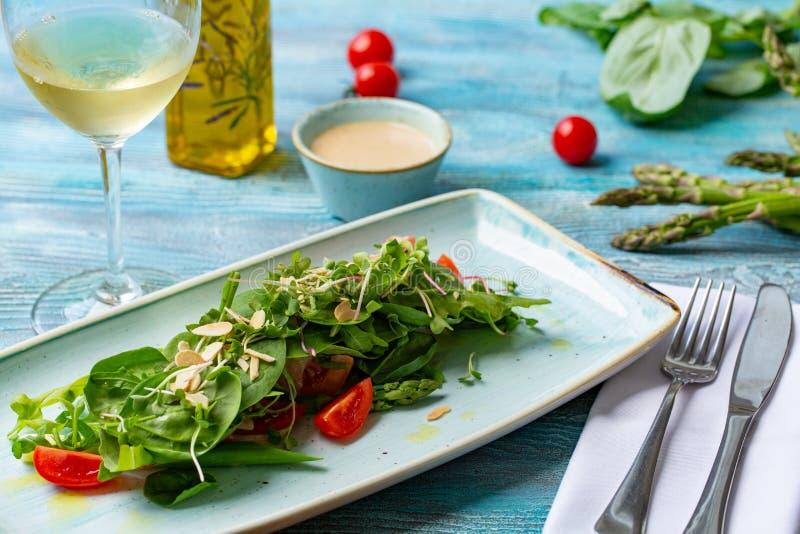 Ensalada fresca con los tomates y los verdes mezclados arugula, mesclun, mache en fondo de madera Alimento sano imagenes de archivo