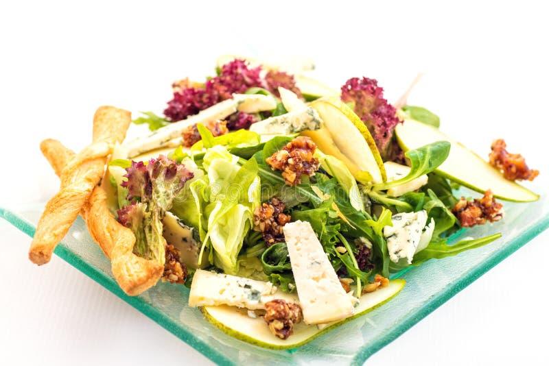 Ensalada fresca de la lechuga con queso verde, la pera y las nueces caramelizadas en la placa de cristal en el fondo blanco, foto imágenes de archivo libres de regalías