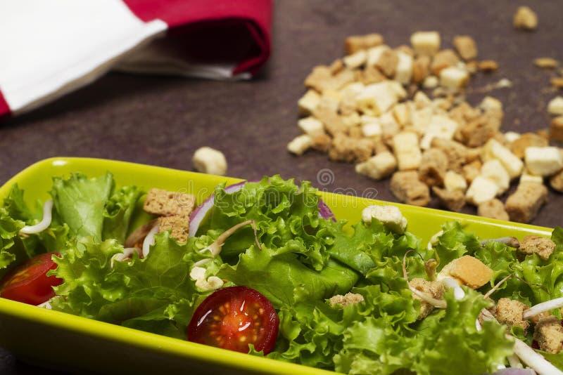 Ensalada fresca de la lechuga y de la cebolla del tomate con el paño rayado rojo, los cordones del pan y la cuchara de madera foto de archivo libre de regalías
